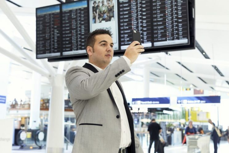 Jack holding a phone up in a busy airport to scan the airport with Aira app.